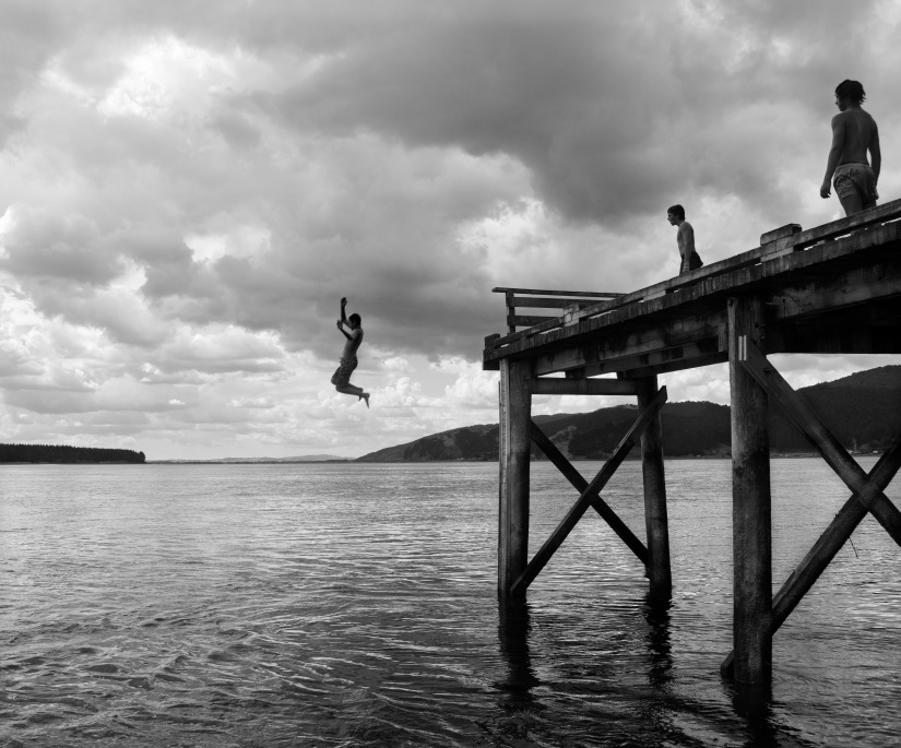 Boys jumping off a wharf