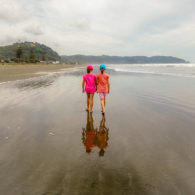Madi and Paige walking along Ohope Beach